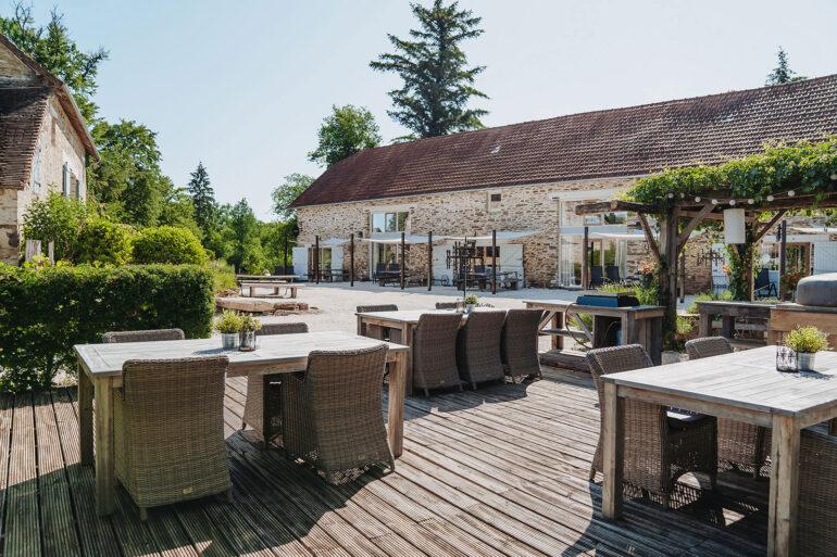 Binnenplaats met eettafels grillplaat en pizzaoven op vakantiedomein La-Bastide in de Haute-Vienne