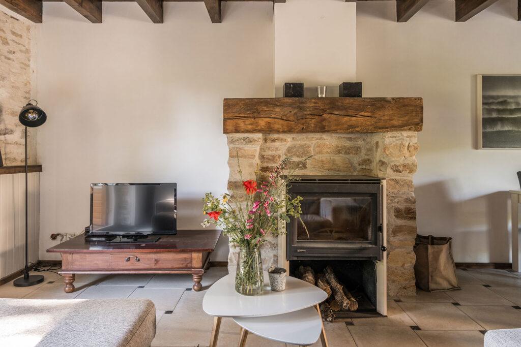Vakantiehuis Bretagne La-Bastide woonkamer haardschouw met houtkachel en televisie
