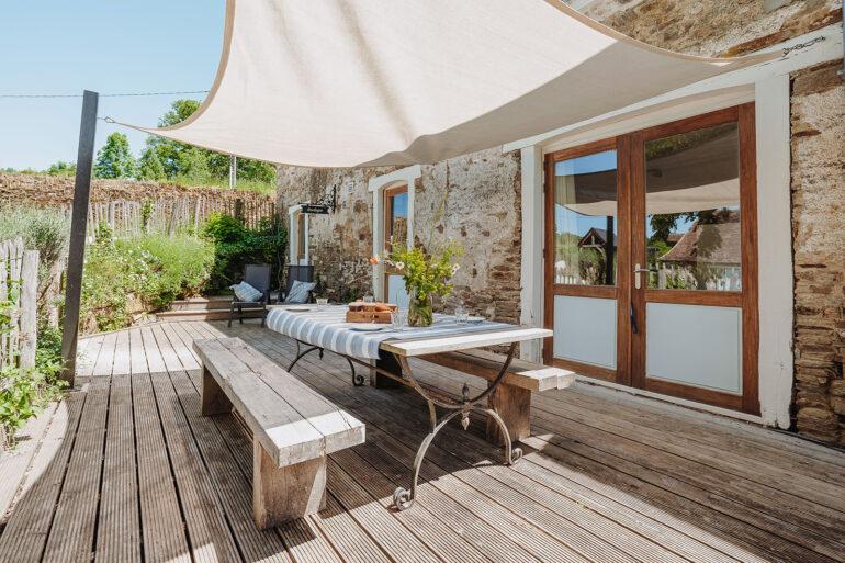 Vakantiehuis Dordogne La-Bastide terras natuurstenen eettafel met zonnedoek voor schaduw