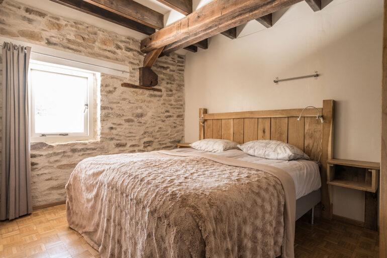 Vakantiehuis Limousin La-Bastide slaapkamer met mooie houten achterwand en nachtkastje