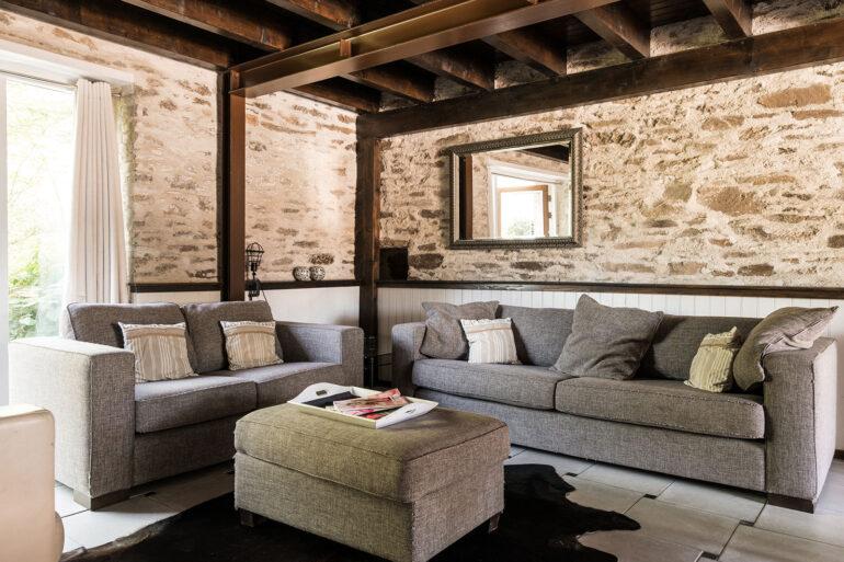 Vakantiehuis Limousin La-Bastide woonkamer grote zithoek met twee bankstellen en leren stoel