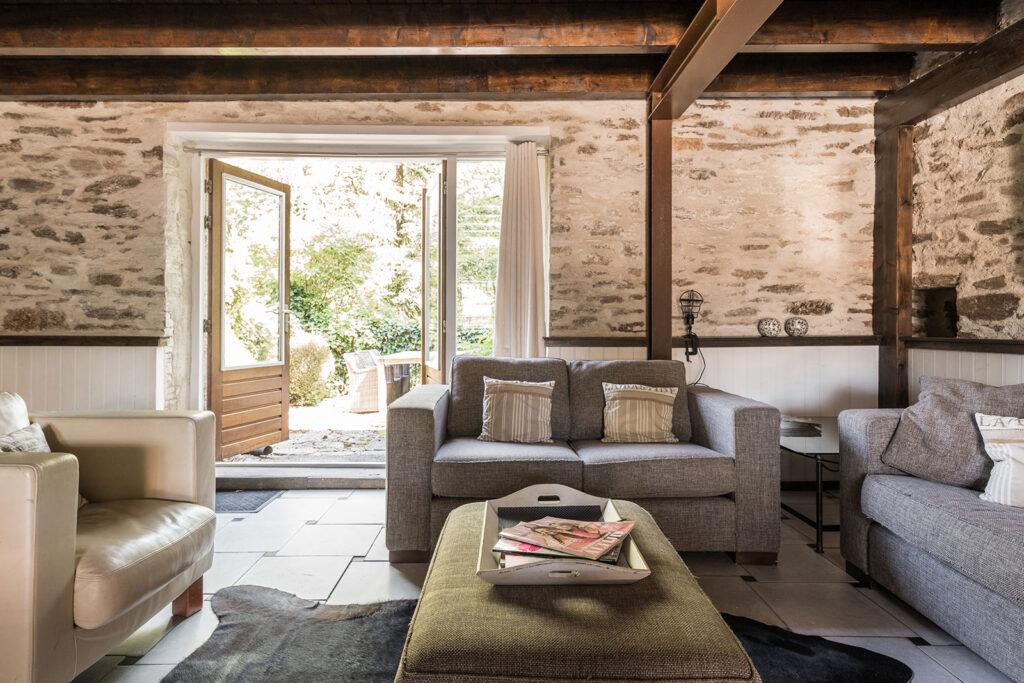 Vakantiehuis Limousin La-Bastide woonkamer zithoek met openslaande deuren naar het achter terras