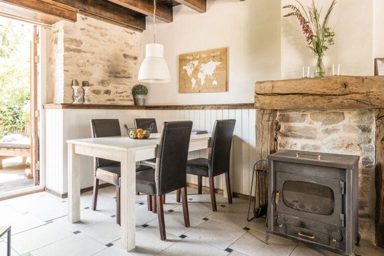 Vakantiehuis Loire La-Bastide woonkamer gezellige eettafel met sfeervolle haardschouw met houtkachel