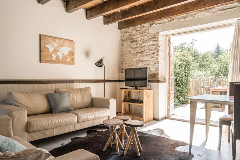 Vakantiehuis Normandië La-Bastide woonkamer zithoek met televisie openslaande deuren naar het achter terras